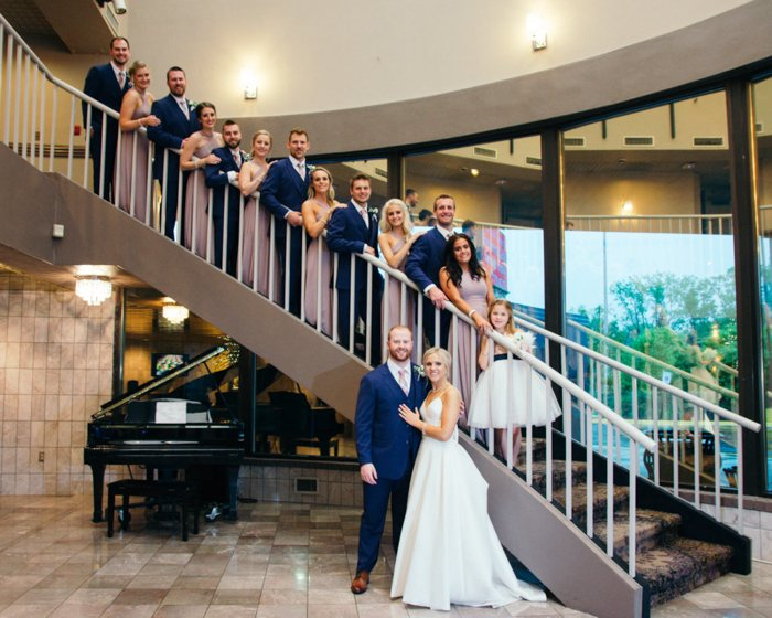 Large group photo of a wedding entourage posing on a big curved staircase, the bride and groom at the bottom in front, a baby grand piano nearby