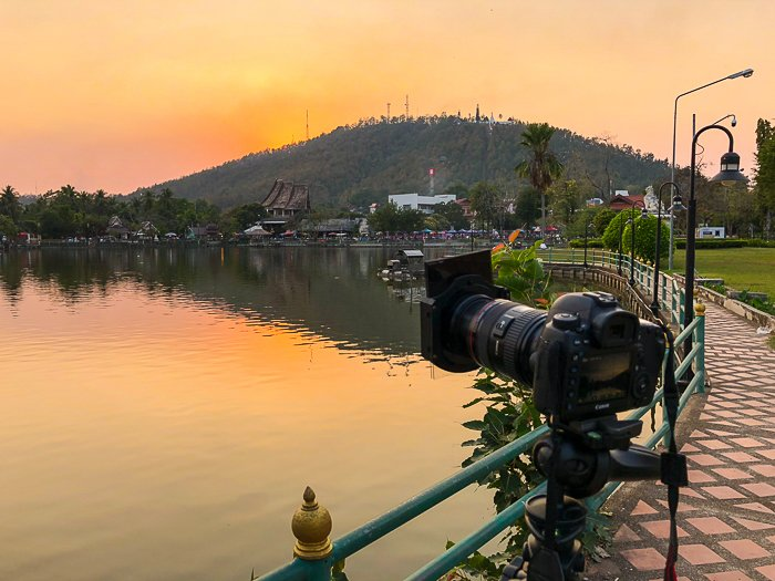 camera set up on a tripod at the shore, looking over at the mountain, sea, and horizon in the golden sunset - How to Take Stock Photos That Sell