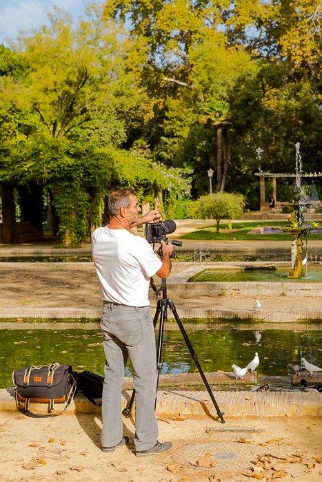 photo of a man at the lake shore, setting up his camera on a tripod
