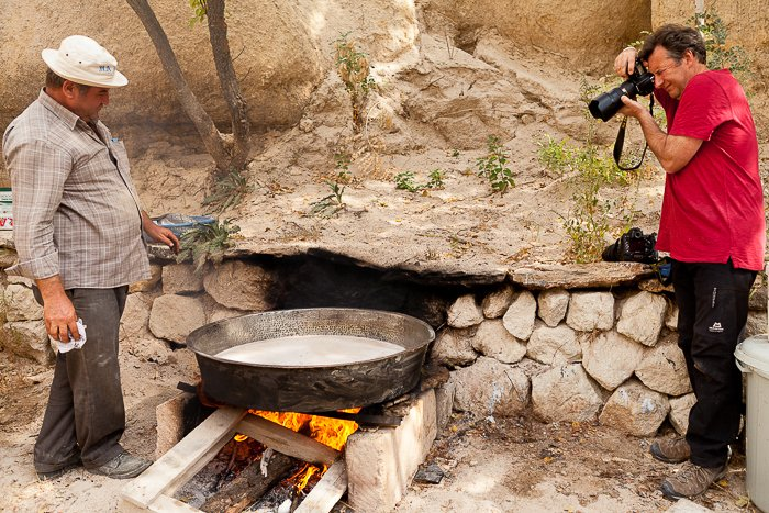two men outdoors with a big pan on a fire of an old stone over, man in the red shirt with a DLSR taking a photo