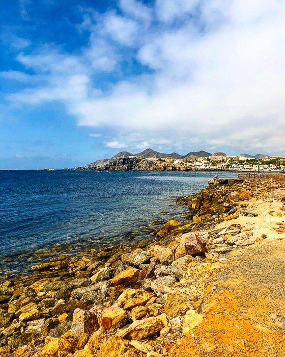 photo of a golden rocky beach, deep blue sea, and cloudy blue sky
