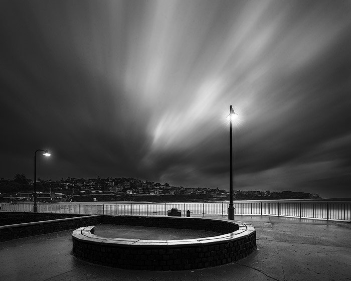 black and white long exposure photo of a seaside lit by lamps at night