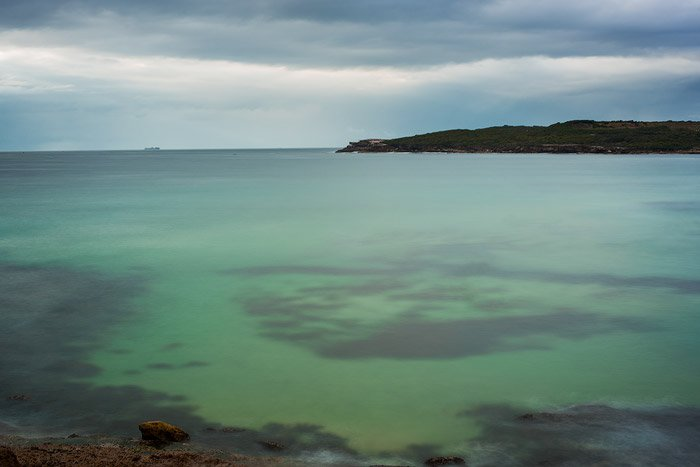 sea green and cloudy skies, a small mountain on the horizon