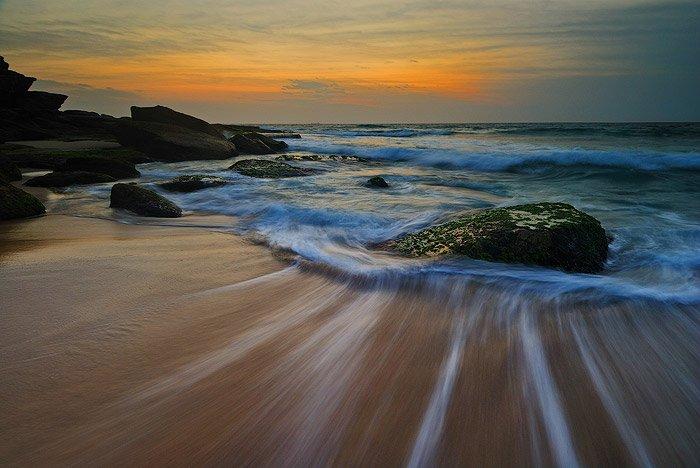 sunset seascape. water trails on the shore, rocks showing up in the foamy waves, golden sunset on the horizon