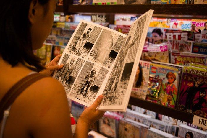 A girl reading a magazine in a shop - magazine photographer tips