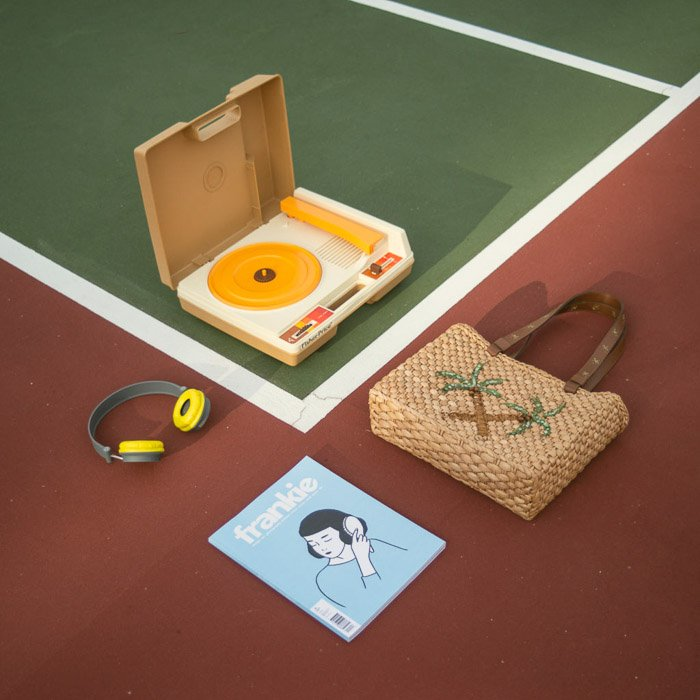 Overhead shot of a record player, bag, magazine and earphones laid out on a sports track