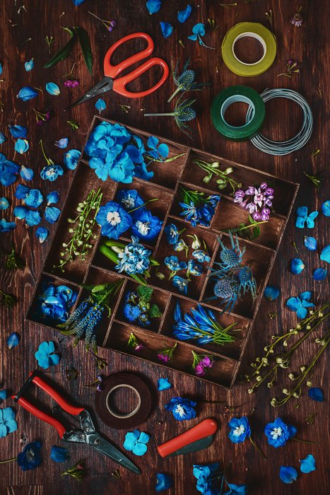 sky blue flowers, pink and purple petals and leaves in a wood box, more petals and leaves on a wood table background, with scissors, clippers and tape