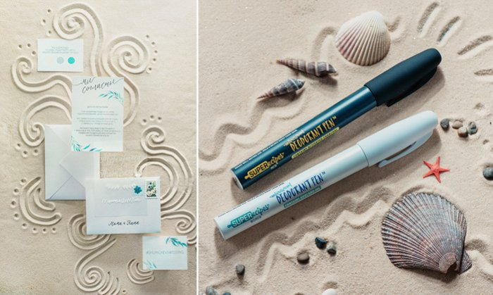 minimalistic invites and envelopes, shells, and art markers on fine brown sand. curly fun designs traced into the sand around them.