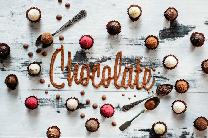 Word chocolate made from glazing with chocolates, candies and tea spoons on a white wooden background. Food typography concept. Sweet flatlay.