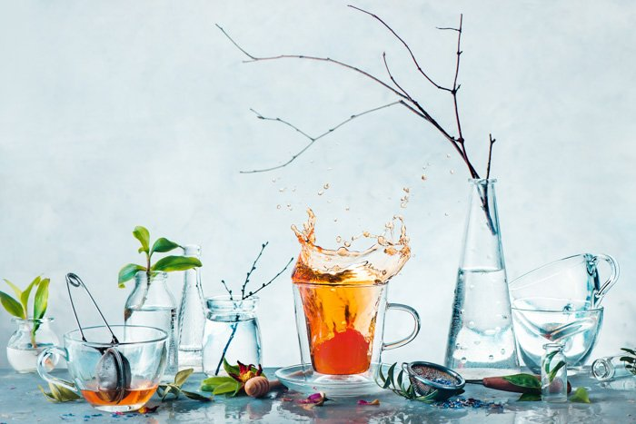 Tea cup with a dynamic splash and glass bottles with green plants and tree branches in a high-key spring still life. Cleanness and freshness concept