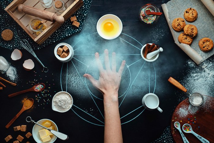 styled flatlay of a hand on a dark table, flour scattered, baking ingredients and tools scattered