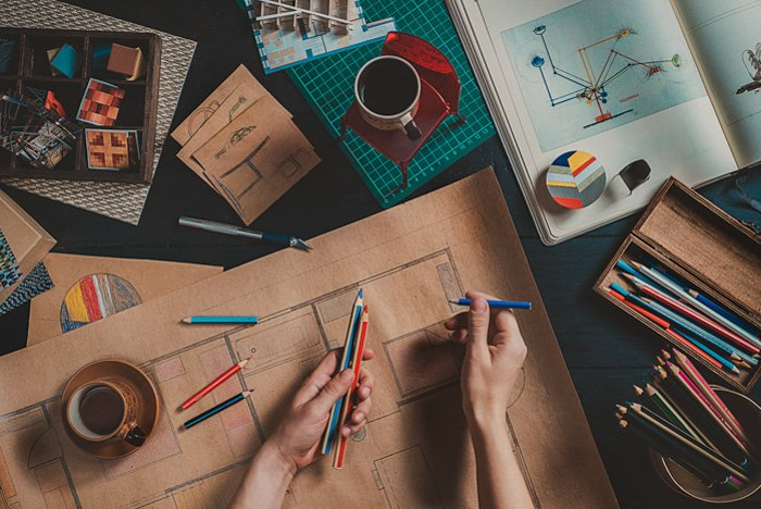 flatlay photo of hands holding drawing pencils, a large brown paper on a table with other drawing materials and coffee