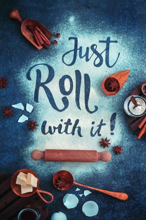 Just roll with it. Lettering in flour, surrounded by baking materials: rolling pin, wooden spoon, ingredients, on a dark blue teal background