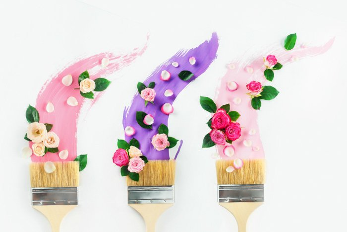 Paintbrushes with paints in pink and violet shades, roses and petals, on a white background. Painting spring creative flat lay. Home decoration concept.