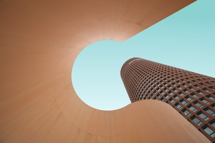 Cool architecture photo looking up through a sculptural element beside a tall multi windowed building