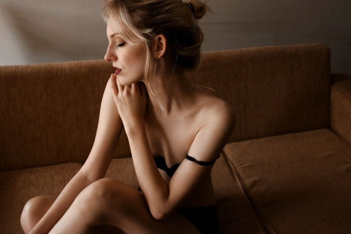 Sensual boudoir photography of a blonde woman in black underwear posing on a beige couch