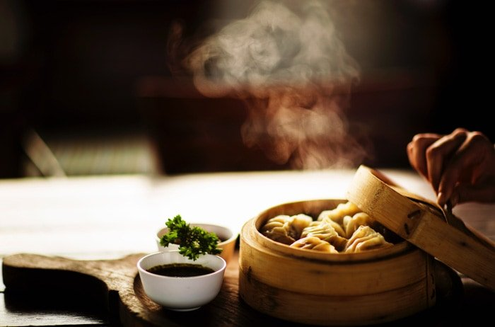 A person opening the lid on a steaming bowl of dumplings, beside two small bowls of sauce on a wooden chopping board