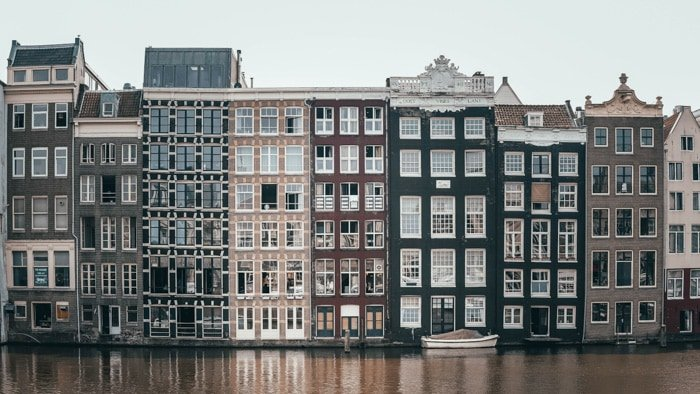 A row of buildings by a canal on an overcast day