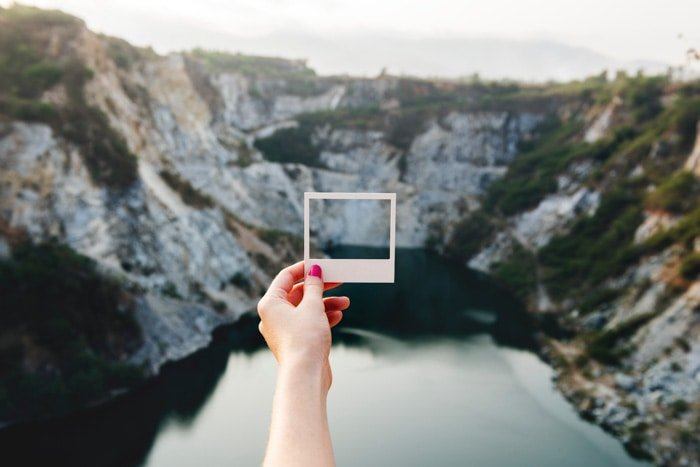 A photographer holding a Polaroid frame out against a mountainous landscape over a lake