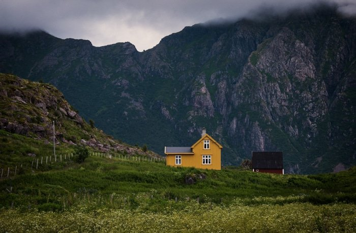 Two buildings surrounded by a beautiful mountainous landscape on a cloudy day