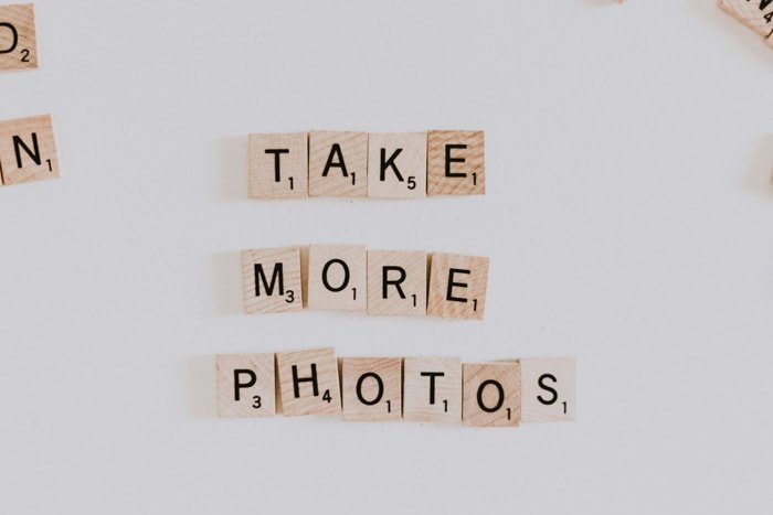 Wooden scrabble pieces spelling 'take more photos' on white background