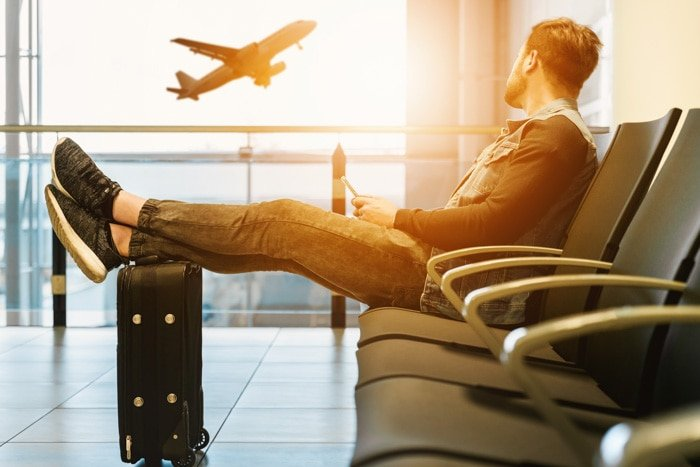 A man sitting in an airport waiting area, watching an airplane ascending from the window