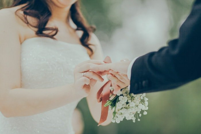 Dreamy close up wedding portrait of a bride placing a ring on the grooms finger