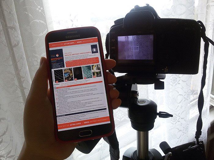 A hand holding a smartphone with the photzy website open