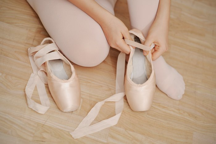 close up of a girl putting on her ballet shoes - photo props