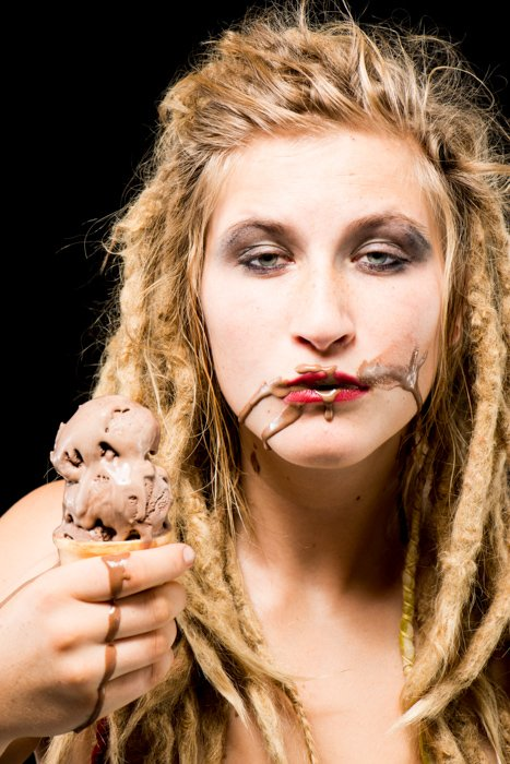 A blond girl with chocolate ice-cream on her face against a black background - photo props