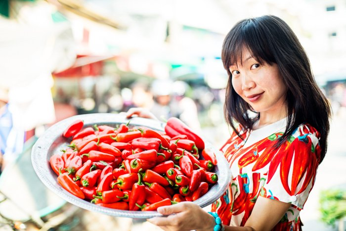 Young pretty Asian woman at an outdoor market with chili peppers. - photography props