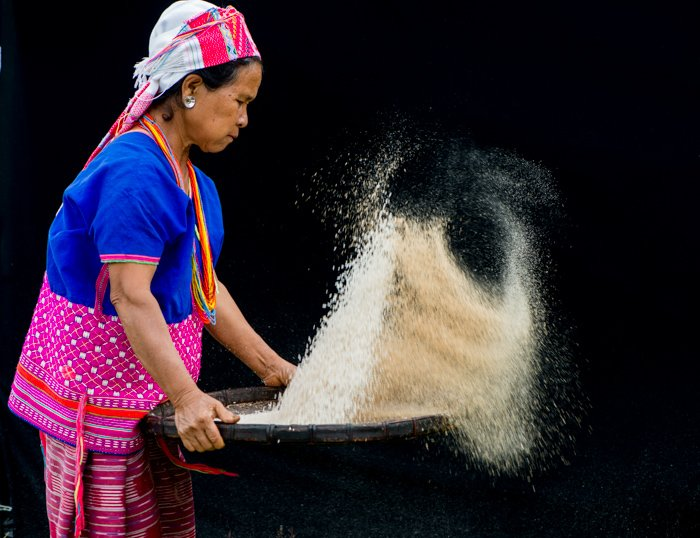 A woman holdoing a tray full of rice against a dark portrait background - using photography props