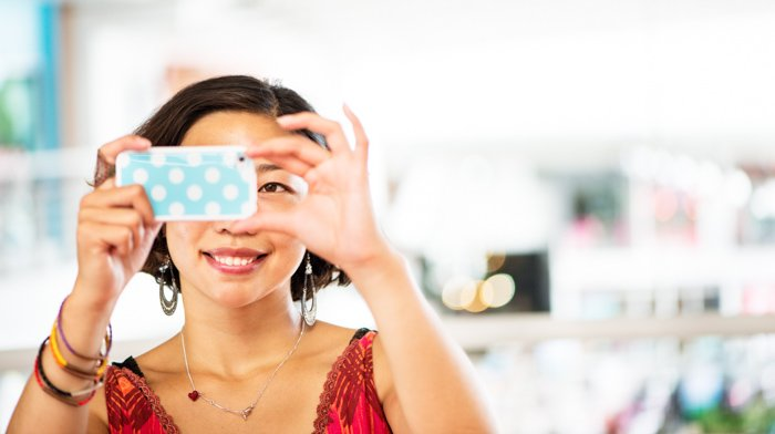 Woman using a smart phone to take a photograph.