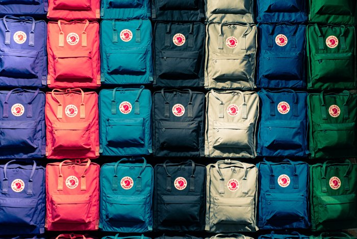Product photography of several backpacks lined up and organised by colour