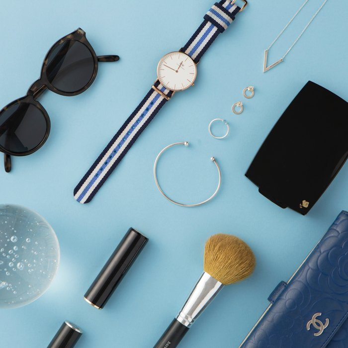 flatlay of woman's accessories on a light blue background: watch, earrings, sunglasses, brush, wallet