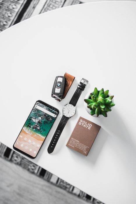 flatlay of man's pocket contents: watch, smartphone, keys, pocket notebook
