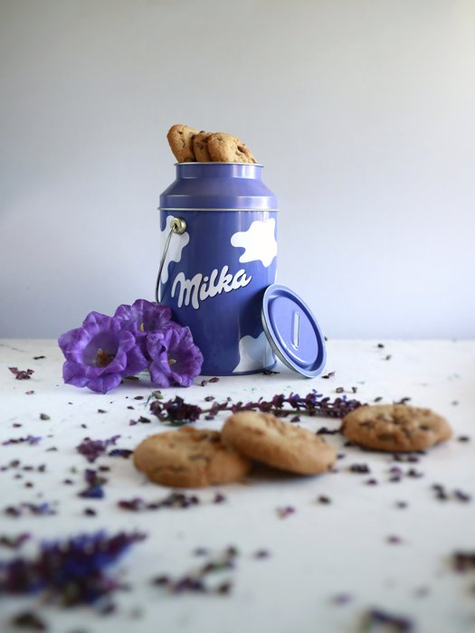 purple and white tin of cookies, purple flowers next to it, cookie and chocolate crumbs on the table