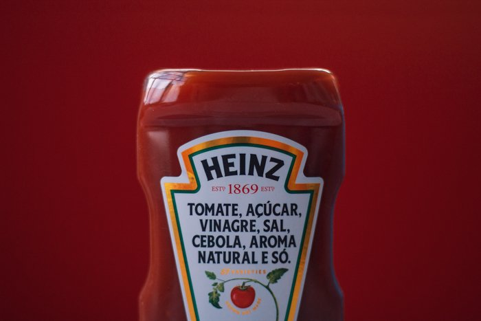 close up of half of heinz ketchuo bottle against matching dark red background