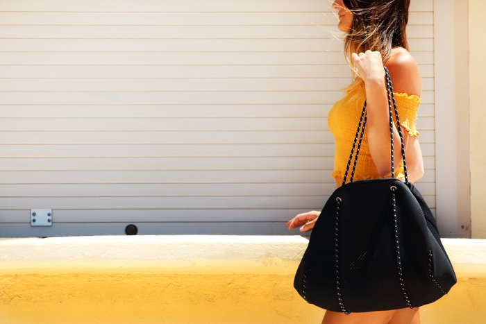 woman in a yellow top and black skirt, with black bag, a white and yellow wall behind her