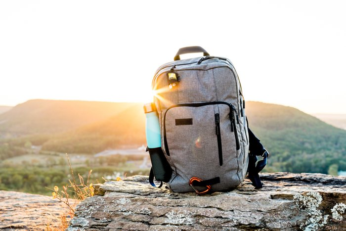 grey backpack sitting on a grey rock outdoors, the sun rising from behind the desert hills on the horizon