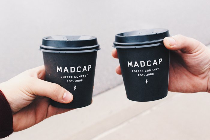 two hands holding black take out coffee cups