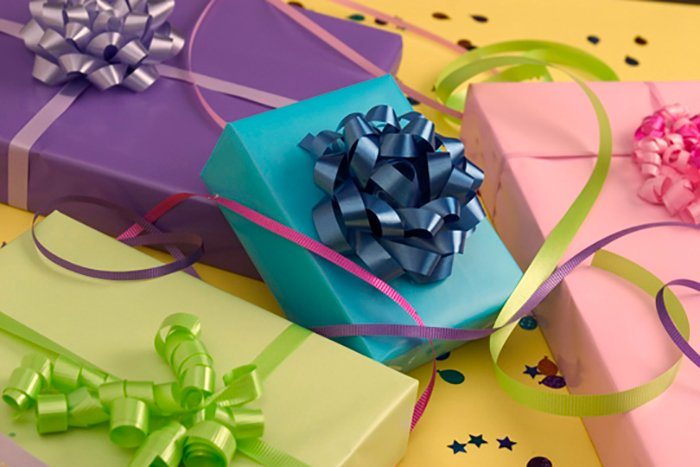 Still life product shot of birthday presents wrapped in different coloured paper and party streamers