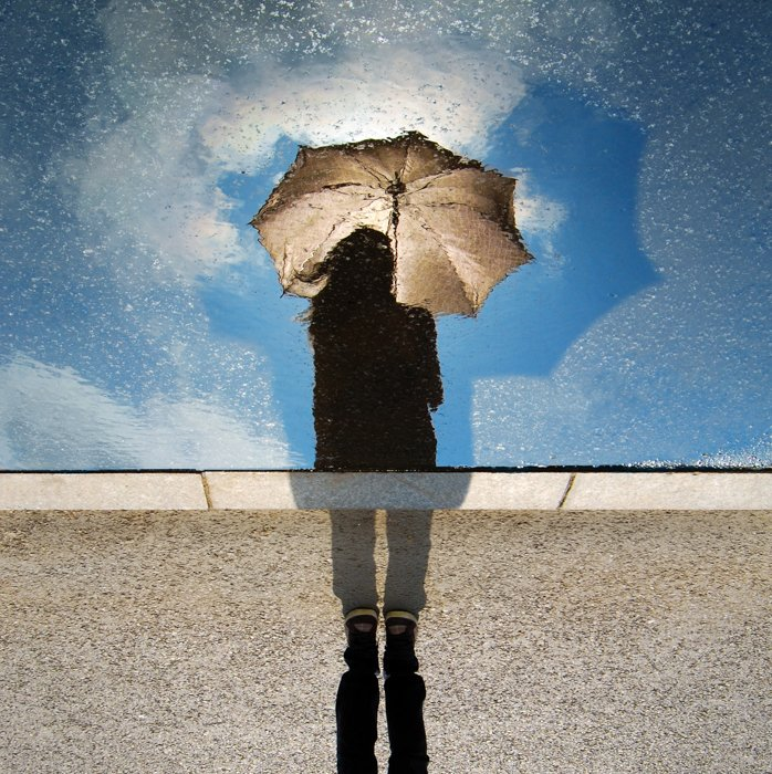 Creative rain photo of a person holding an umbrella, reflected in a rain splashed window