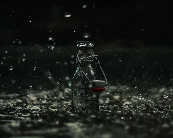 Atmospheric product photography of glass bottle splashed with falling rain
