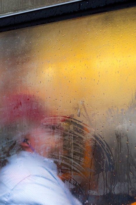 A portrait of a person shot through a rain splashed window
