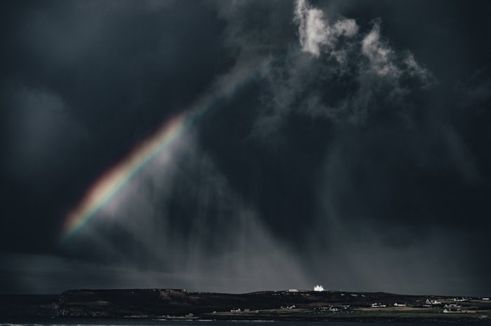 A dramatic landscape with a rainbow breaking through a stormy sky