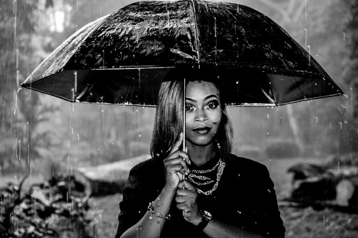black and white portrait of a woman holding an umbrella in the rain