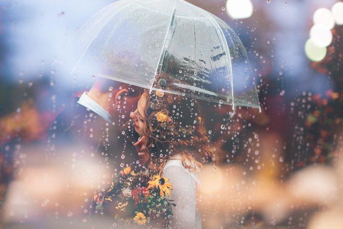 Dreamy wedding photography of a couple embracing under an umbrella