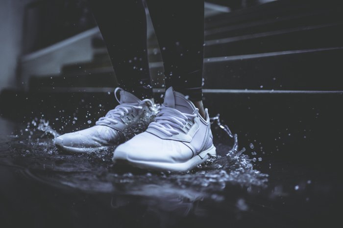 Dark and moody rain image of a persons feet stomping in a puddle shot with fast shutter speed