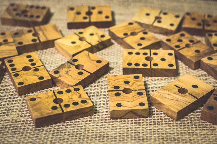 close up of several wood domino tiles on a brown table.